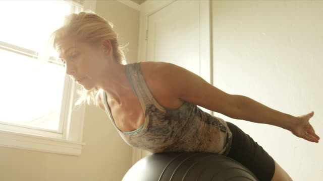 A mature woman doing situps with an exercise ball in her home gym.