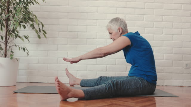 Mature woman doing stretching exercises on the floor at home.