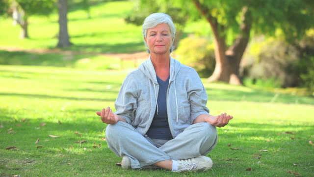stockvideo's en b-roll-footage met mature woman doing yoga / cape town, western cape, south africa - lotuspositie