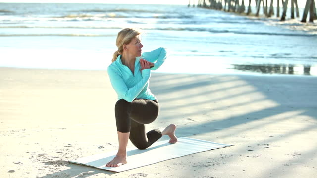 mature woman doing yoga exercises on the beach - yoga stock videos & royalty-free footage