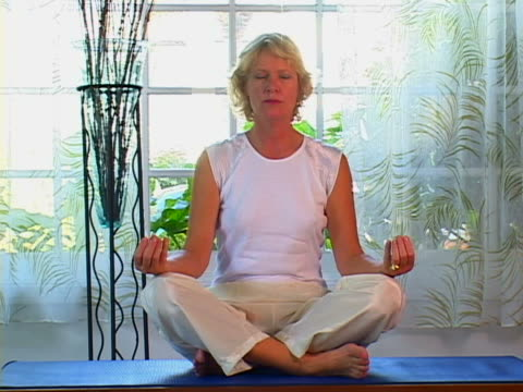 mature woman doing yoga - lotusställning bildbanksvideor och videomaterial från bakom kulisserna