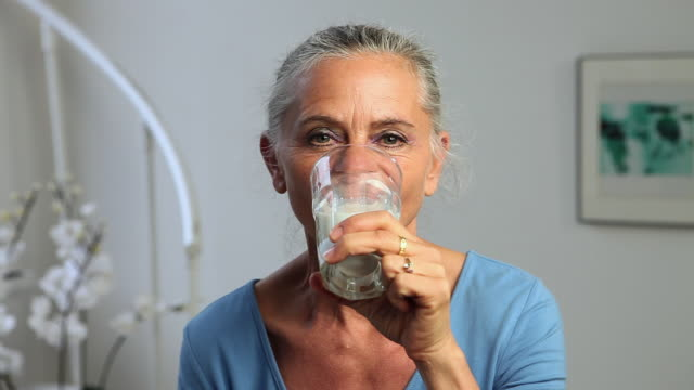 mature woman drinking a glass of milk - osteoporosis stock videos & royalty-free footage