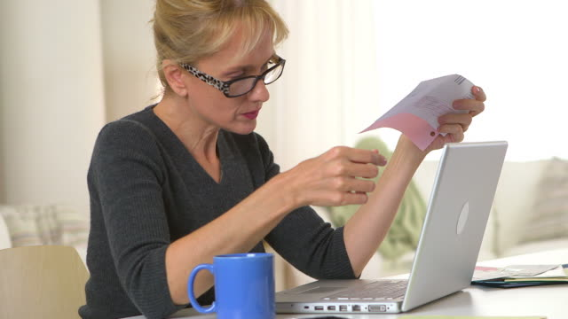 Mature woman drinking coffee and using laptop to pay bills