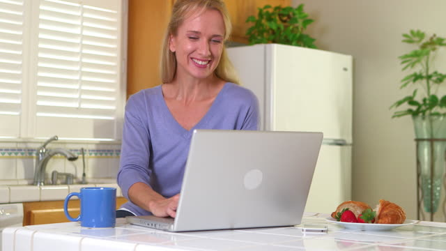 Mature woman drinking coffee and using laptop