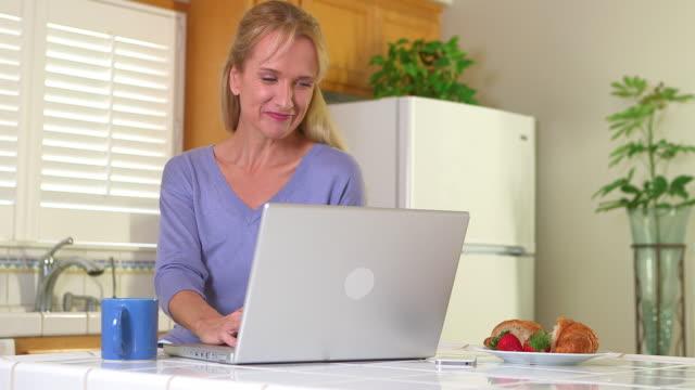 vídeos de stock, filmes e b-roll de mature woman drinking coffee and using laptop - só uma mulher madura