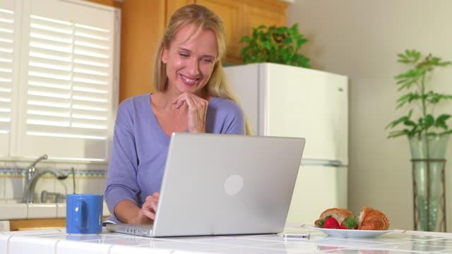 vídeos de stock e filmes b-roll de mature woman drinking coffee and using laptop - só uma mulher madura