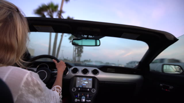 mature woman driving in a convertible along the beach - blonde hair stock videos & royalty-free footage
