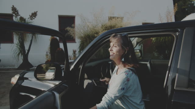 mature woman driving to a hotel in the desert. - 到着点の映像素材/bロール