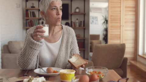 mature woman eating a breakfast at dining table at home. - bread stock videos & royalty-free footage