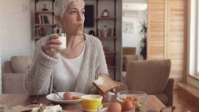 mature woman eating a breakfast at dining table at home. - prima colazione video stock e b–roll