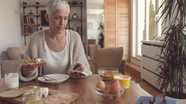 Mature woman eating breakfast and reading text message on mobile phone.