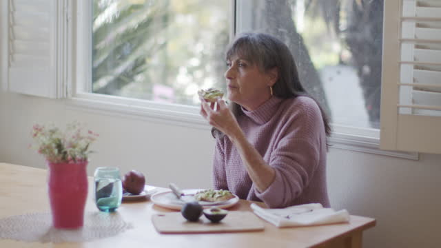 mature woman eating eating avocado toast at home - day stock videos & royalty-free footage
