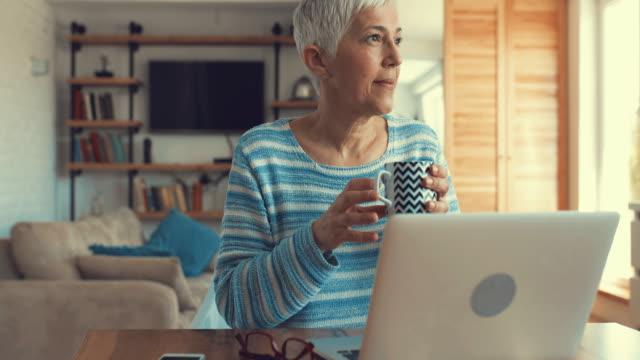 vidéos et rushes de femme mature jouir dans la tasse de café tout en utilisant l'ordinateur portable à la maison. - living room