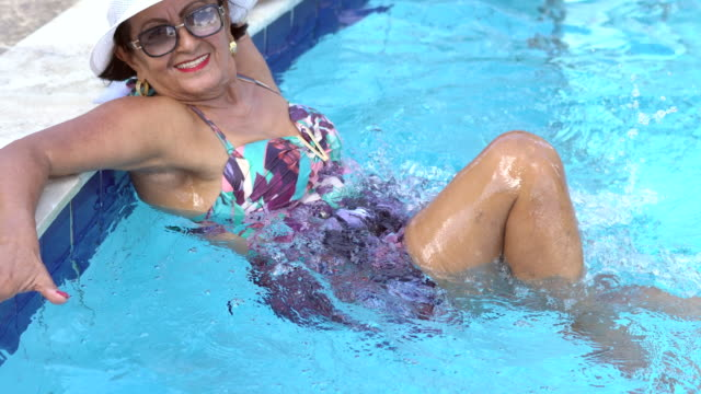 mature woman enjoying in the resort swimming pool - uv protection stock videos and b-roll footage