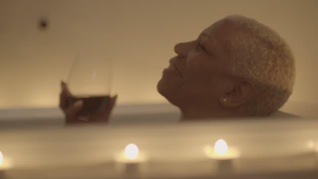 mature woman enjoys a relaxing bath. - rött vin bildbanksvideor och videomaterial från bakom kulisserna