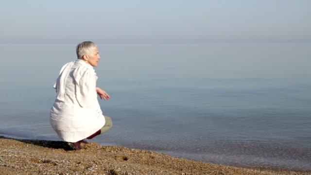 Reife Frau genießt einen Spaziergang am Strand am Meer