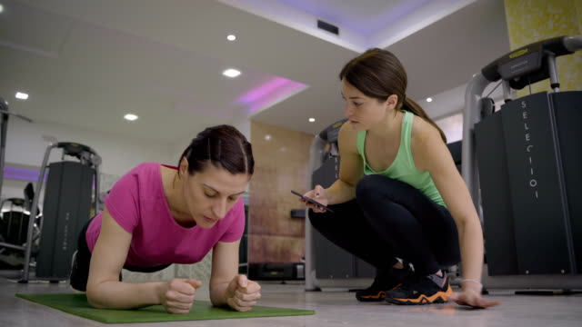 mature woman exercising - doing a plank in gym with personal trainer. - durevolezza video stock e b–roll