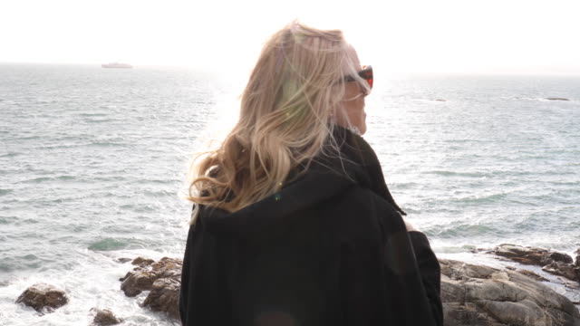 mature woman explores windy headland - coastal feature stock videos & royalty-free footage