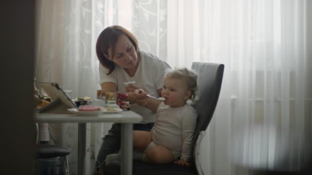 mature woman feeding baby boy yogurt for breakfast - tempo reale video stock e b–roll