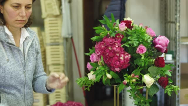 Mature woman florist working in flower workshop alone