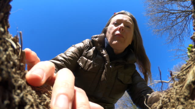 Mature Woman Gardening and Looking at Hole in Dirt