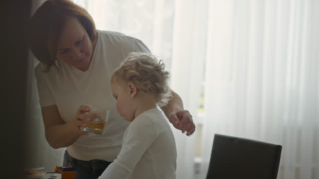 mature woman giving apple juice to baby boy playing in kitchen in the morning - orange juice stock videos & royalty-free footage