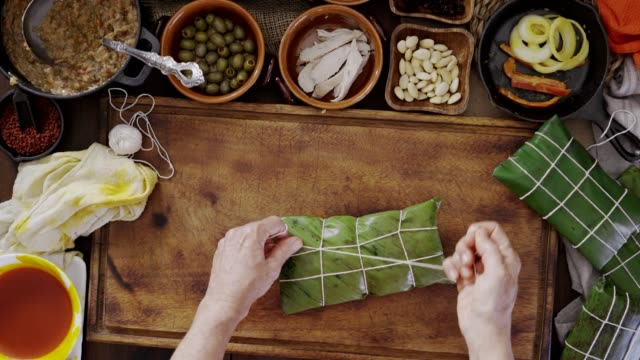 vídeos de stock e filmes b-roll de mature woman hands tying hallaca, venezuelan traditional christmas food. actual set with ingredients: stew, almonds, olives, onions, bell pepper, chicken, pork meat and coloring with onoto - cordel