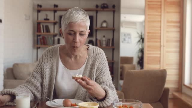 Reife Frau, dass ein Frühstück und gehen weg Anzeichen beim Blick in die Kamera.