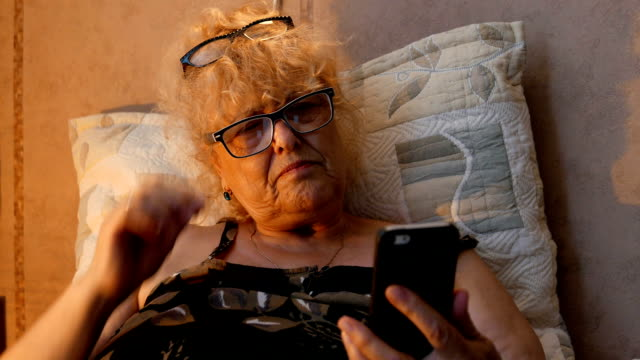 Mature woman having a trouble looking at her phone with the wrong glasses