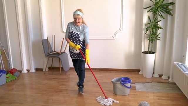 stockvideo's en b-roll-footage met rijpe vrouw die pret heeft terwijl het schoonmaken van haar huis - alleen één oudere vrouw