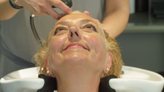 cu mature woman having her hair washed at a hairdressers - kopf nach hinten stock-videos und b-roll-filmmaterial