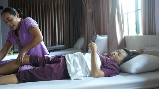 mature woman having relaxing  with Thai massage and using phone