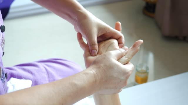 Rijpe vrouw met ontspannen met Thaise massage, Trigger vinger