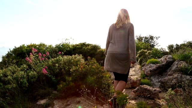 Mature woman hiker explores Mediterranean hilltop