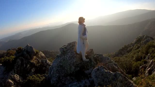 mature woman hikes along mountain ridge crest, look off to view - one mature woman only stock videos & royalty-free footage