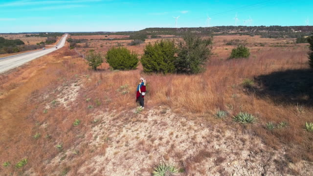 vídeos de stock e filmes b-roll de mature woman hiking in the arid highland in texas, usa. aerial drone video with the forward camera motion. - estados da costa do golfo