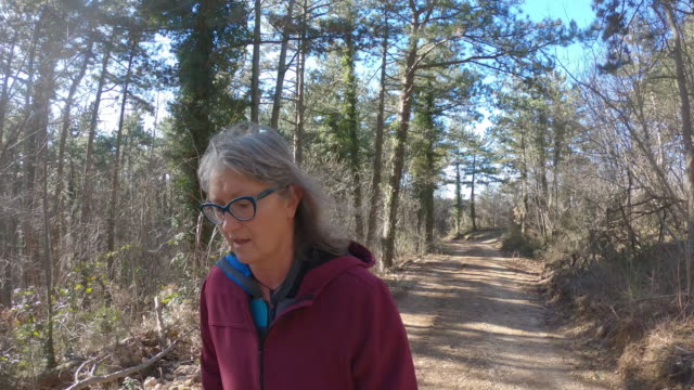 Mature Woman Hiking on Country Road Thru Forest