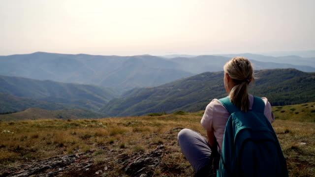 vídeos de stock e filmes b-roll de mature woman hiking-relaxing on the top of the mountain - mulheres maduras