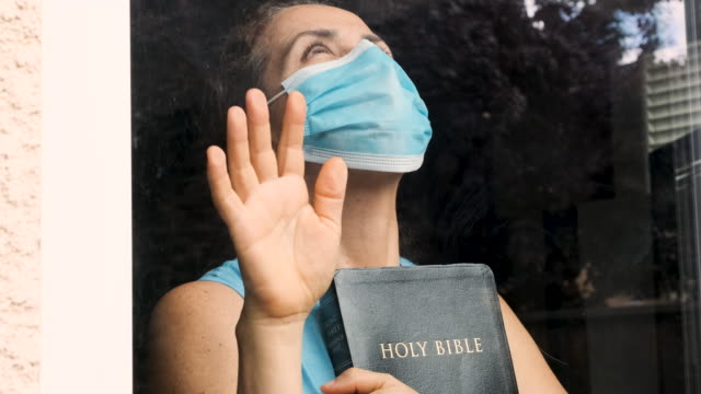 mature woman holding a bible wearing a surgical mask looking through a window - cristianesimo video stock e b–roll