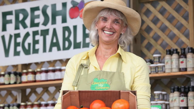 MS TU TD Mature woman holding box of tomatoes at farmer's market / Richmond, Virginia, USA