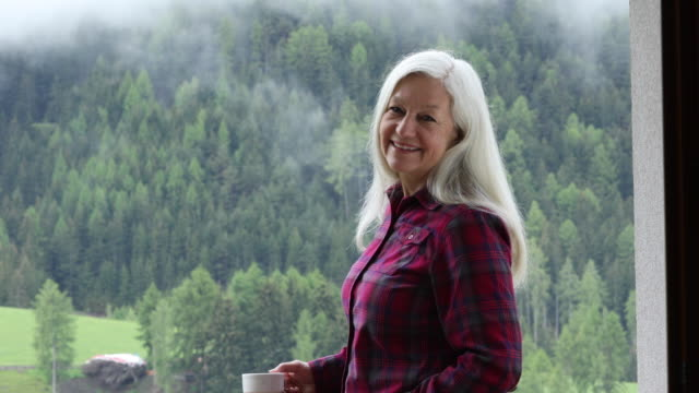 mature woman holding coffee cup by forest in san pietro, italy - capelli grigi video stock e b–roll