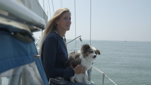 mature woman holding her dog on a sailboat - 日常から抜け出す点の映像素材/bロール