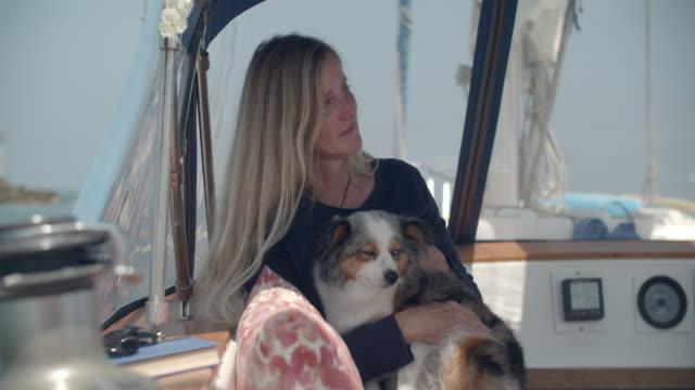 stockvideo's en b-roll-footage met mature woman holding her dog on a sailboat - australische herder