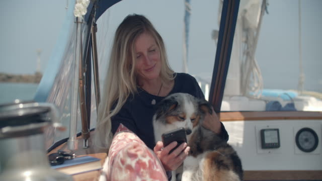 vidéos et rushes de mature woman holding her dog on her sailboat - 50 54 ans