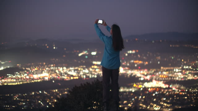 mature woman holding her phone up to the sky at night - photography stock videos & royalty-free footage