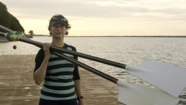 mature woman holding oars on shoulder. - canottaggio video stock e b–roll