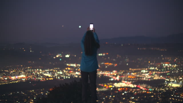 mature woman holding up her phone to the sky at night - telekommunikationsgerät stock-videos und b-roll-filmmaterial