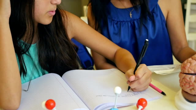 Mature woman home schooling preteen daughter, teaching science class