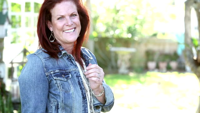 mature woman in denim jacket turns toward camera, smiles - denim jacket stock videos and b-roll footage