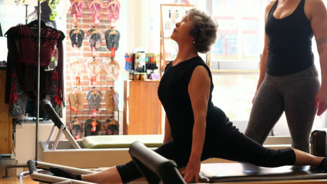 MS Mature woman in front split on pilates reformer during class while female instructor adjusts form